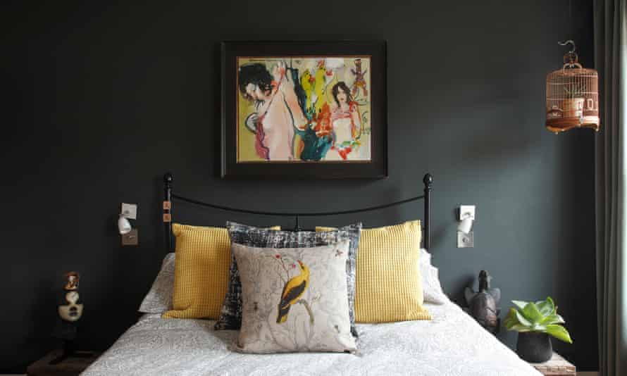 A painting above a bed, and a bird cushion