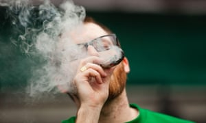 A man smokes from an enormous joint