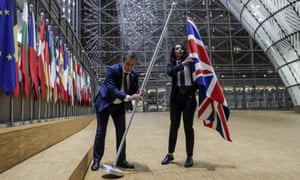 Staff remove the union flag from the European council building in Brussels on Brexit Day.