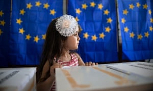 A little girl waits for her mother to vote in the European Parliament elections in Baleni, Romania