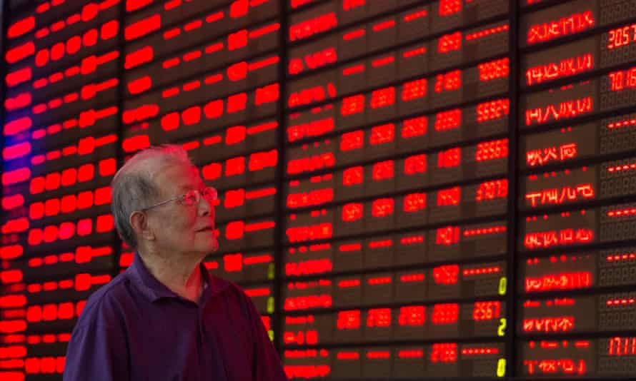 An investor looks at the price of shares in Nanjing, China.