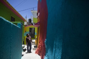 Alfonso Santiago Reyes looks up at the newly-painted facade of his home