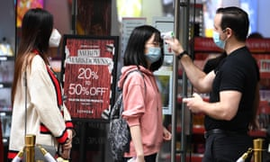 Shoppers have their temperature checked on entry to a store in Sydney on Boxing Day.