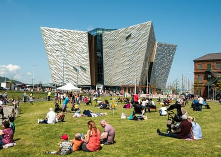People relax and enjoy the sunshine on the grass area in front of the Titanic Building.