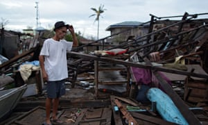 A Filipino villager stands next to his damaged house in the typhoon-hit town of Casiguran, northern Manila.