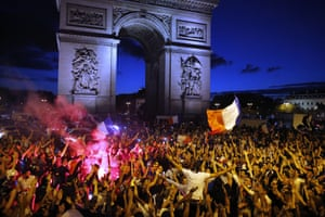French fans celebrate in front of The Arc de Triomphe on the Champs Elysees in Paris.