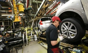 A worker produces a car at Nissan's assembly plant