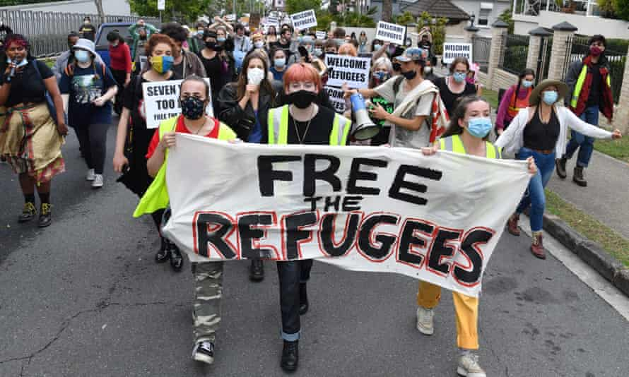 protesters march with a free the refugees sign