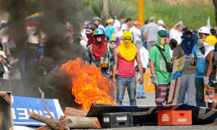 Anti-government protesters stand near a barricade