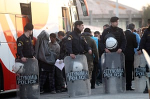 People take their belongings from a bus before they get on a ferry for Turkey behind riot police