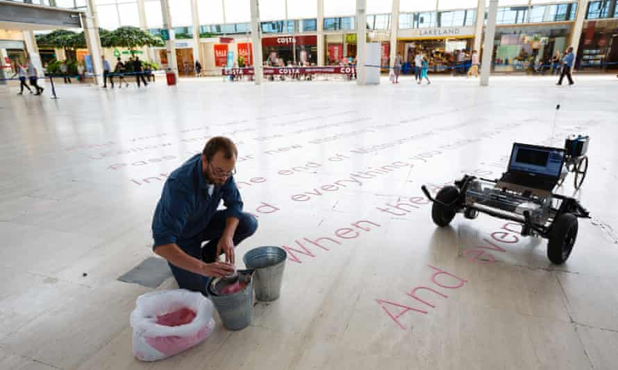 Artist Gijs Van Bon and his robot SKRYF, which is writing some of Jackie Kay's poetry at the Centre:MK shopping mall in Milton Keynes