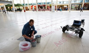 Artist Gijs Van Bon and his robot SKRYF, which inscribed Jackie Kay poetry at the Centre:MK shopping mall in Milton Keynes in 2014.