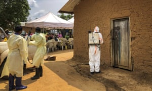A worker from the World Health Organization (WHO) decontaminates the doorway of a house on a plot where two cases of Ebola were found