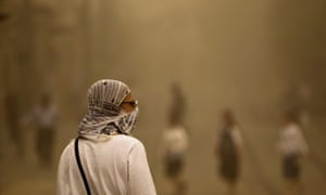 A pedestrian walks with a covered face during a sandstorm in Jerusalem.