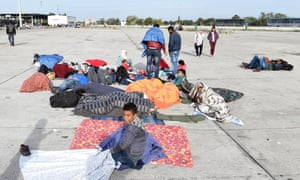Migrants who arrived via Hungary rest at a collection point in a parking lot of the former border station on the Austrian side of the Hungarian-Austrian border near Nickelsdorf.