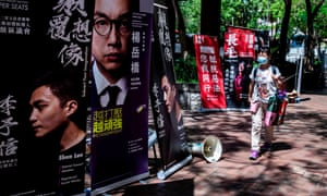 A woman walks past campaign signs during primary elections in Hong Kong. Up to 600,000 voted in what was seen a rebuff for the new security laws.
