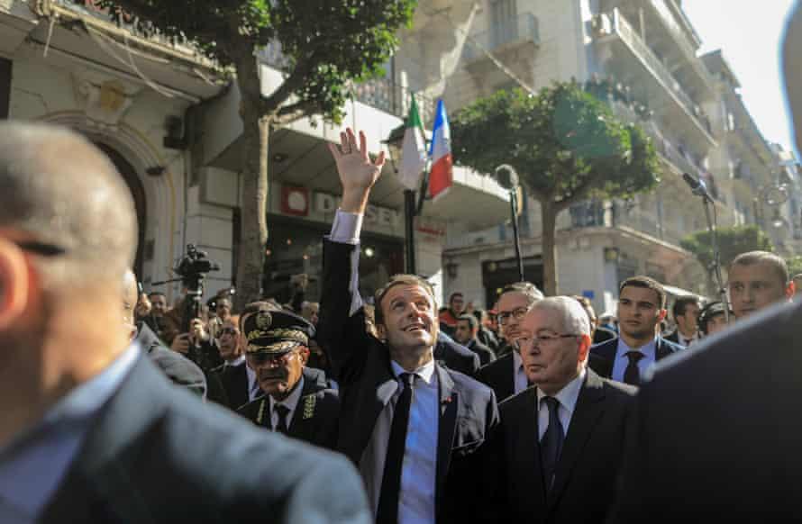 France's president, Emmanuel Macron, waves at onlookers as he walks with Algeria's senate president, Abdelkader Bensalah, in Algiers