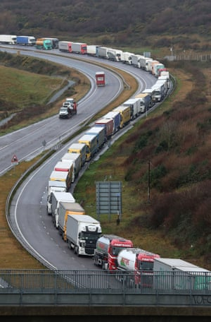 A long queue of lorries in the slow lane of a curving dual carriageway