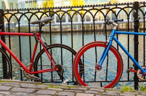 Two bikes, red and blue, leaning on the fence at the river bank. Camden town, London, UK.