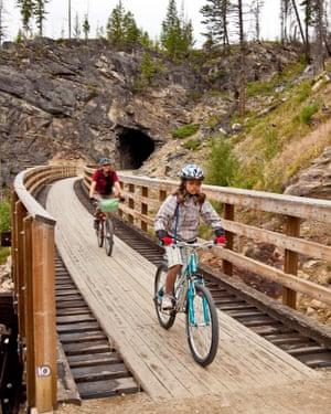 Young family cycling the Kettle Valley Railway Trail through Myra canyon, Okanagan Valley