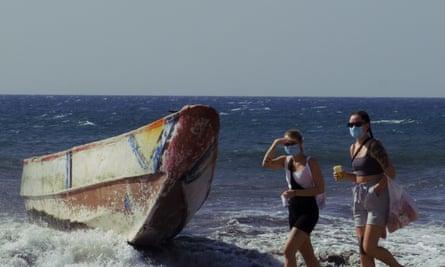 Women walk past a wooden boat used by migrants at Maspalomas beach, Gran Canaria, on 1 November.