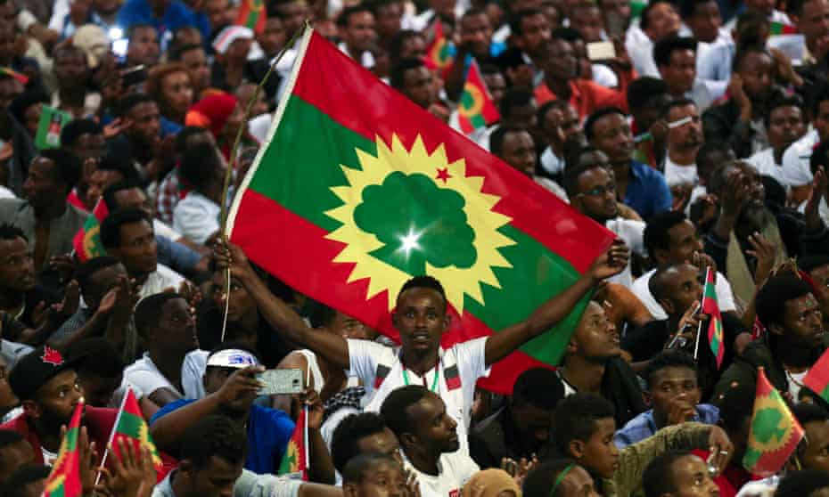 A man holds an Oromo Liberation Front flag as people in Addis Ababa celebrate the triumphant return of Oromo activist Jawar Mohammed
