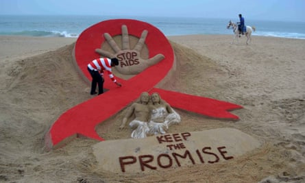 Indian sand artist Sudersan Pattnaik gives the final touches to a sand sculpture on the eve of World AIDS Day