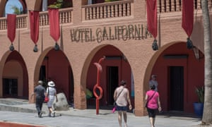 Tourists walk past Hotel California in the town of Todos Santos, Baja California Sur.