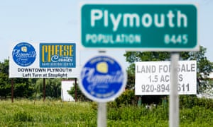 Road signs posted on Highway 57 at the entrance to the town of Plymouth, Wisconsin.