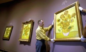 Three versions of Van Gogh's Sunflowers are hung for an exhibition in Amsterdam.
