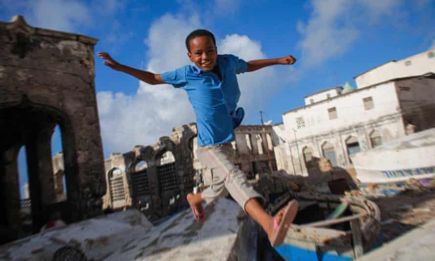 A Somali boy jumps between old fishing boats near Mogadishu's harbour