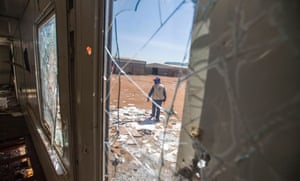 A staff member of the World Food Program (WFP) walks outside as he examines on August 18, 2016 the remains of the logistic base of the United Nations (UN) organisation in the Jebel district in Juba, after it was looted during clashes between Government and opposition forces between July 8 and July 11.