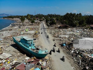 Palu, Indonesia: Motorcyclists travel down a road next to a boat washed ashore by a tsunami triggered by an earthquake on the island of Sulawesi. The death toll has reached 844