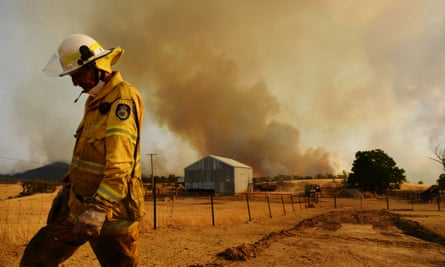 A Rural Fire Service firefighter views a flank of a fire on 11 January in Tumburumba, Australia.