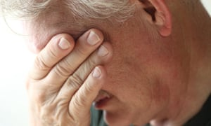 Senior man covers his eyes with his hand in grief or emotional stress.