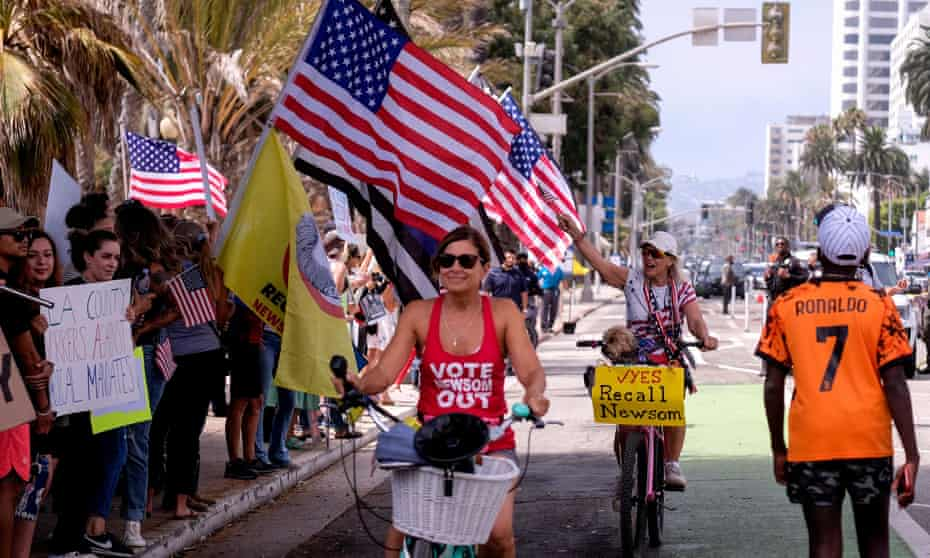 Cyclists with signs in support of the recall effort ride past anti-vaccination protesters taking part in a rally against Covid-19 vaccine mandates, in Santa Monica, California.