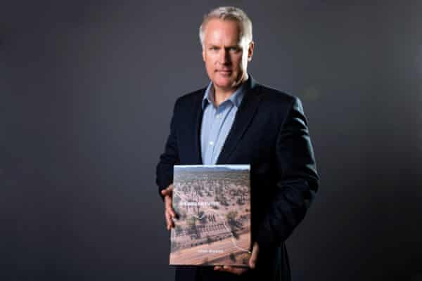 Photographer John Moore poses with his book, Undocumented.