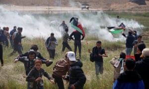 Palestinians run from tear gas fired by Israeli troops during a protest along the Israel border with Gaza.