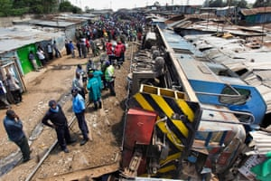 Police officers and rescue workers gather around a freight train that crashed into homes built along the railway track in Kibera slum, injuring several people.
