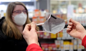 A pharmacist demonstrates how to use an FFP2 mask in Germany where the Brazilian variant has now been detected.