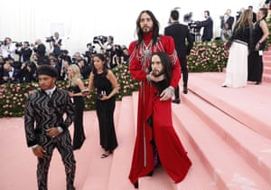 Jared Leto in a long-sleeved red silk Gucci gown, carrying a wax-like replica of his own head