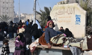 Syrian civilians wait at a checkpoint