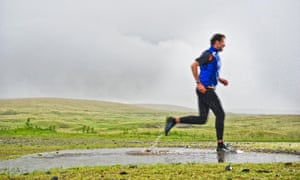 Man jogging in puddle in rural field