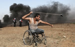 A Palestinian hurls rocks during clashes with Israeli forces along the border with the Gaza strip in May 2018.