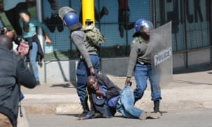 Zimbabwe Republic Police drag away a protester in Harare
