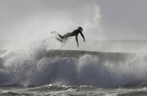 Christchurch, New Zealand A surfer jumps clear of his board while enjoying winter waves at New Brighton beach