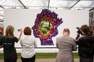 Visitors take pictures of the Behind Every Great Florist exhibit featuring the Queen, designed by Veevers Carter