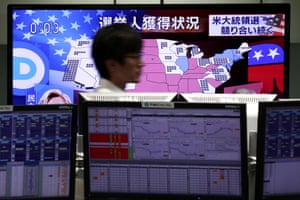 Employee walks past a US map displaying the US presidential elections latest results on TV news channels at a foreign exchange trading company in Tokyo