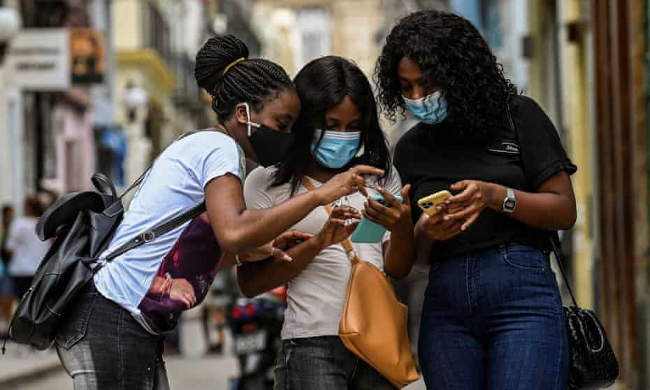 Women use their phones on the street in Havana, Cuba, 14 July 2021.