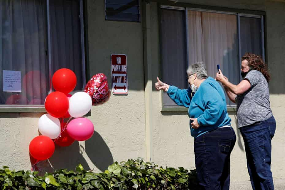Jeannie Richards, left, and Carol Soward bring balloons and a note to their brother Donald Richards, who is among the confirmed cases of Covid-19 at Gateway Care and Rehabilitation Center in Hayward, California.